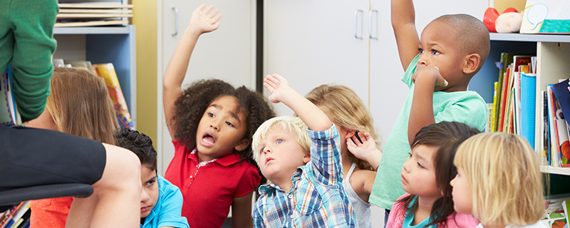Kids raising their hands in class