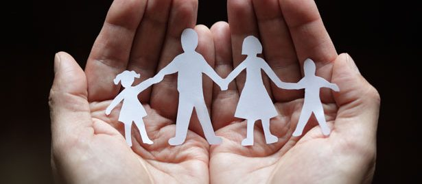 Hands holding family silhouette paper cut-out
