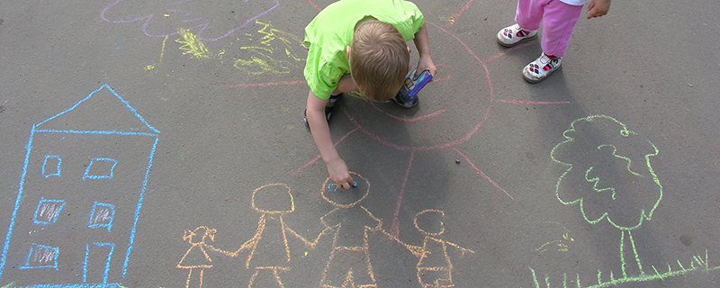 Boy drawing family with chalk