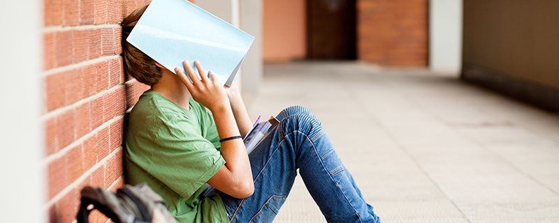Boy with textbook over his head