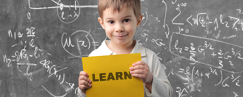 Young boy holding learn sign in front of a blackboard