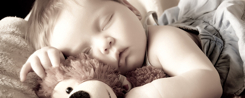 Baby sleeping with teddy bear
