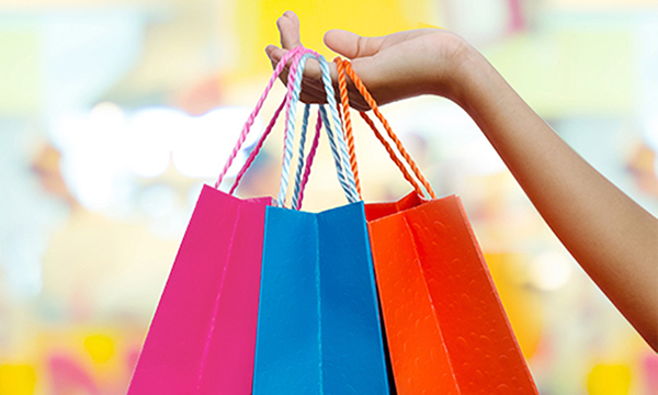Hand holding three colorful shopping bags