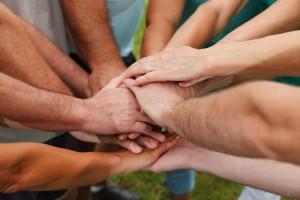 Stacking hands showing teamwork (Shutterstock)