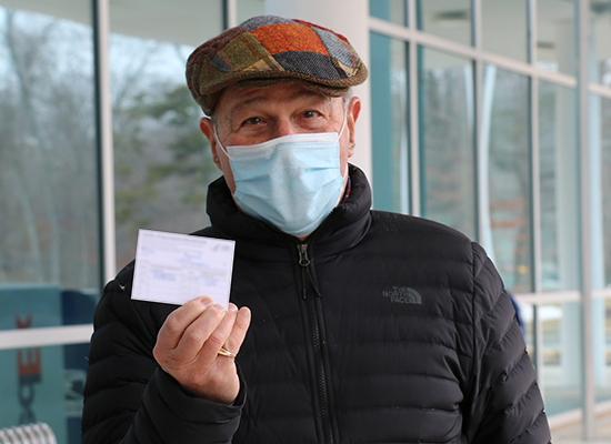 Older male patient holding up his COVID-19 vaccine card after being vaccinated