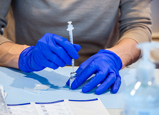 Hands with blue gloves putting a syringe into a vial