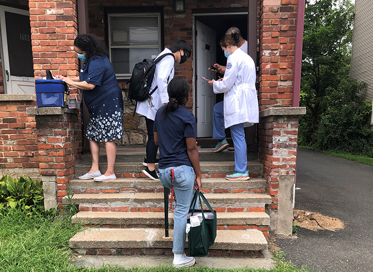 UConn School of Medicine students and staff on the doorstep of a house in Hartford