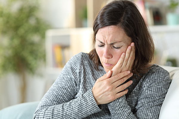 Woman holding her hand against her cheek in pain