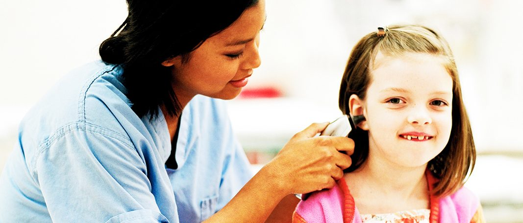Nurse looking in the ear of a patient