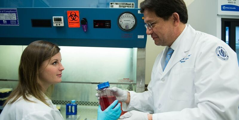 Juan C. Salazar, M.D., M.P.H., with another researcher in his lab
