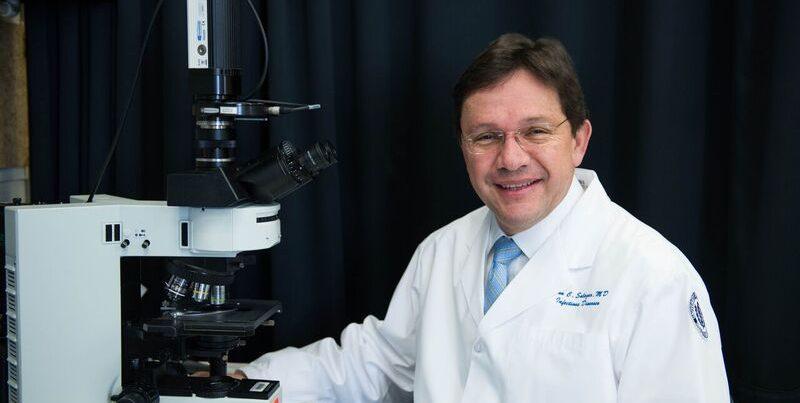 Juan C. Salazar, M.D., M.P.H., at a microscope
