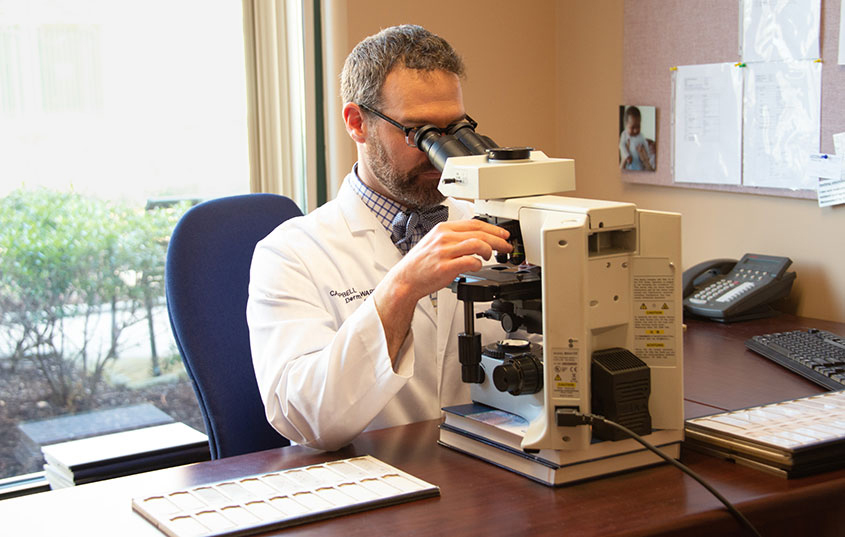 Campbell Stewart, M.D., reviewing a slide under the microscope