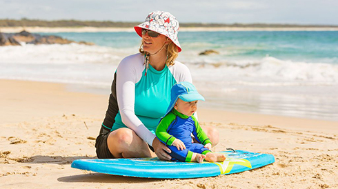 Mom sitting with baby on a surfboard at the beach
