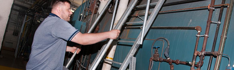 Facilities Management employee climbing a ladder