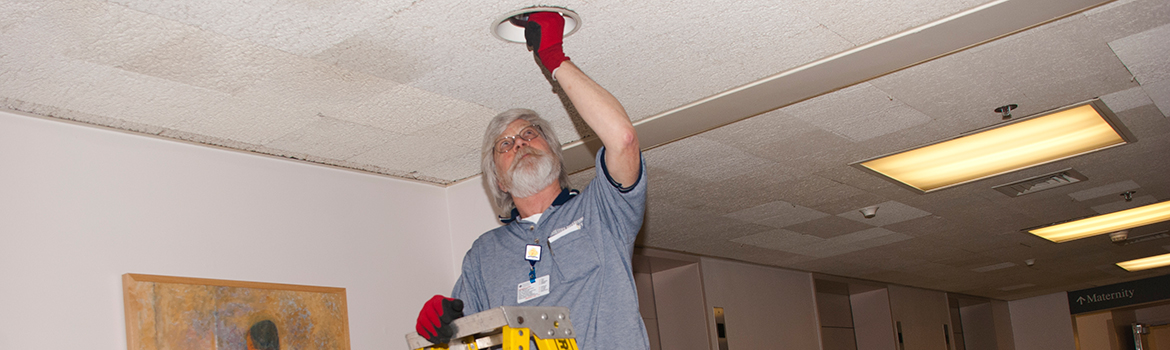 Facilities Management employee changing a lightbulb