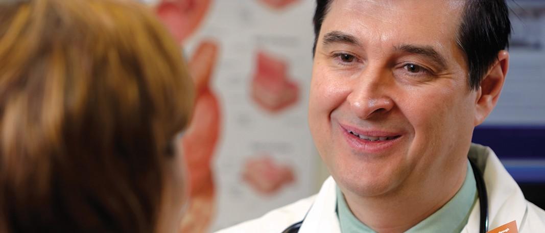 John W. Birk, M.D., FACG, talking to a patient