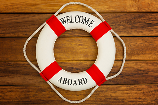 Traditional red and white life preserver on wooden background