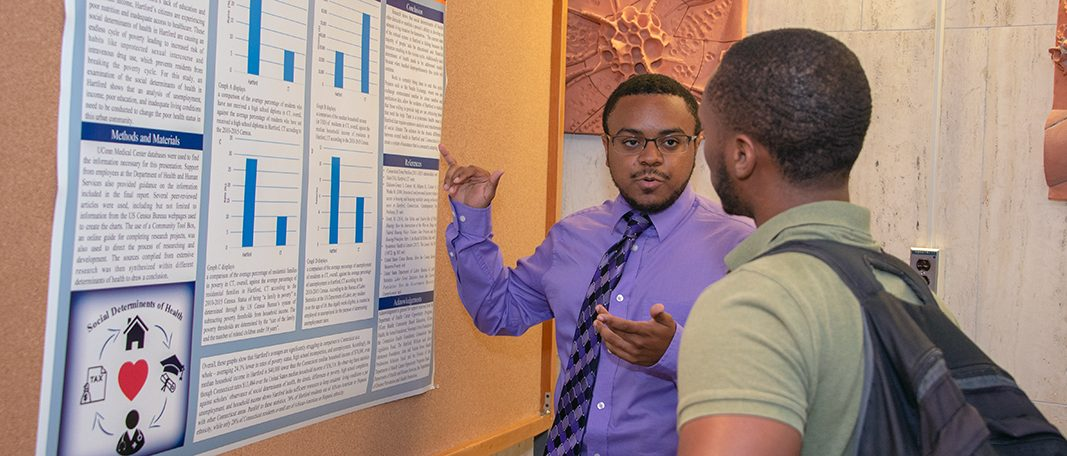 Willie Taylor presenting his health disparities poster to another student