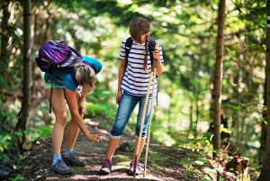 Mother applying tick repellent on daughter before hiking