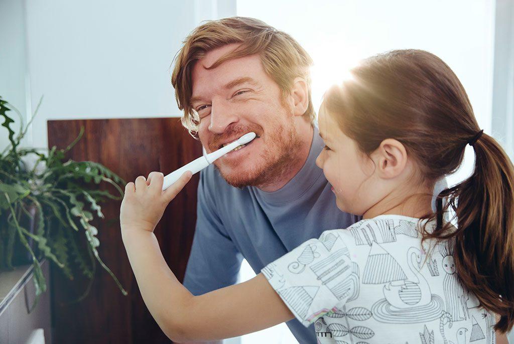 Daughter brushing dad's teeth