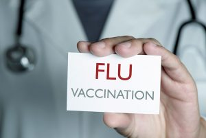 Doctor holding flu vaccination card