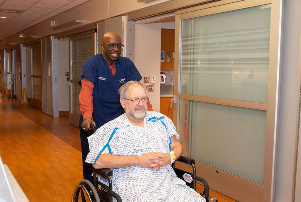 Transport aide with patient in wheelchair