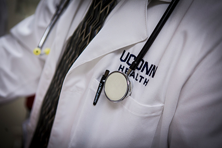 UConn Health lab coat with stethoscope and a pen in the pocket