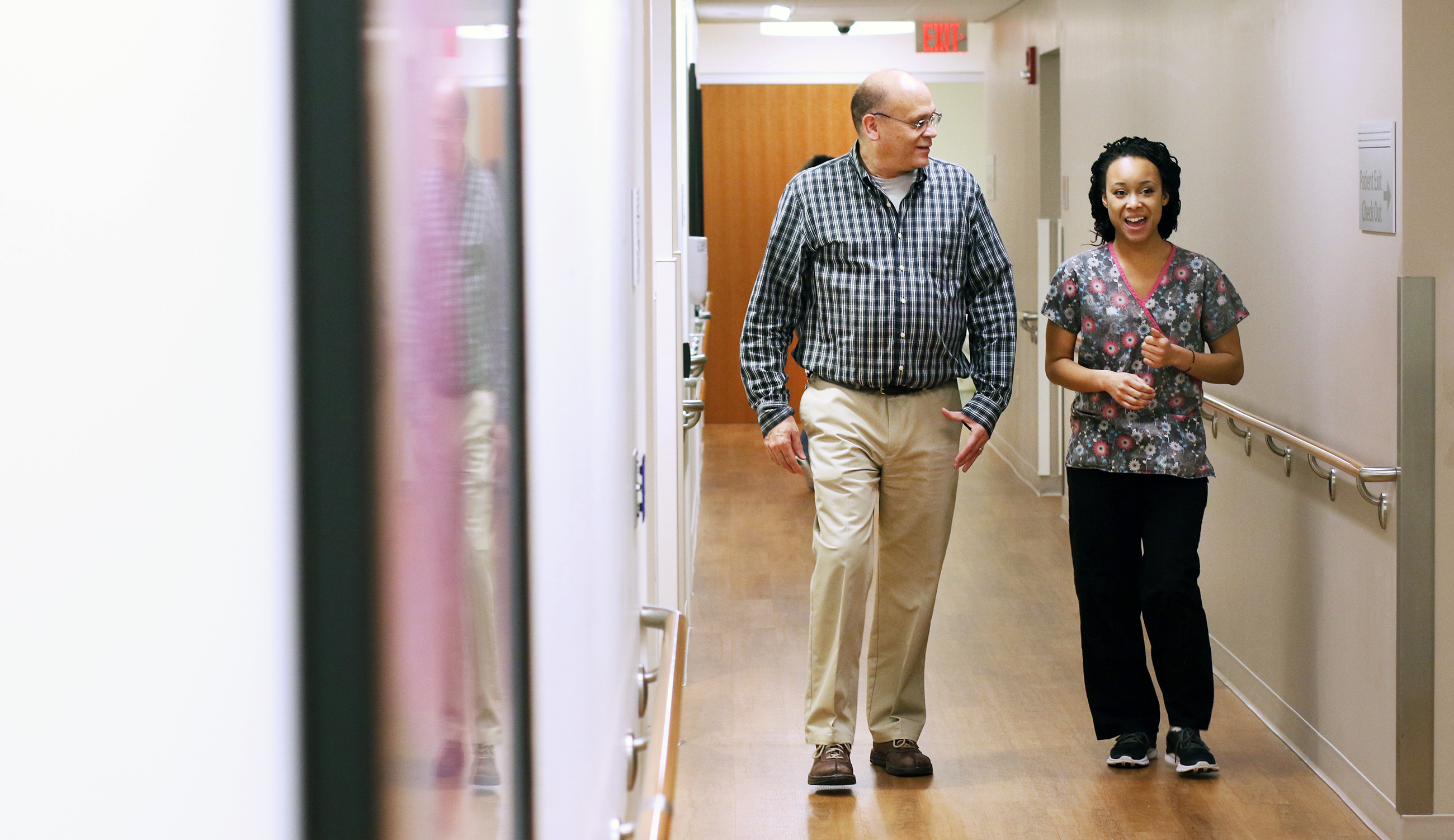 Patient and nurse walk in hallway