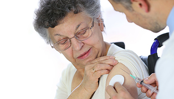 Elderly woman receiving a flu vaccine
