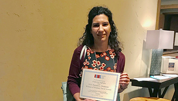 Postdoctoral fellow Dr. Federica Agliano holding a certificate for winning the 2018 Theresa L. Gioannini Women of Science Travel Award