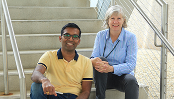 Karthik Chandiran, Ph.D., sitting outside on stairs with Linda Cauley, Ph.D.