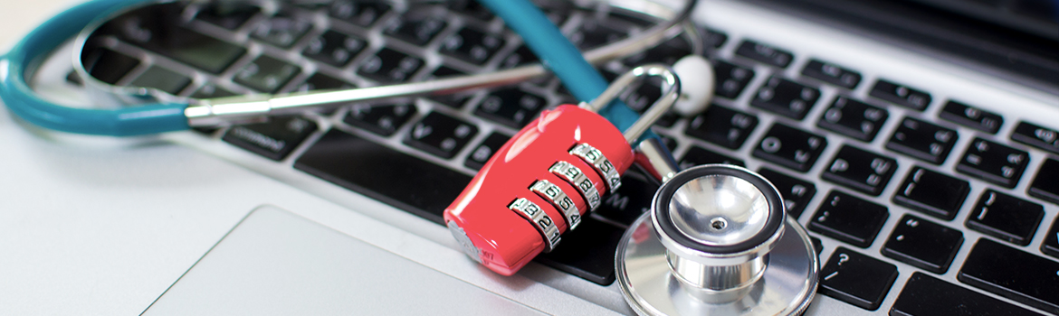 Combination lock and stethoscope laying on top of a laptop computer