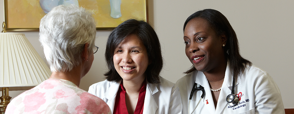 Drs. Anjanette Ferris and Joyce Meng talking to a female patient