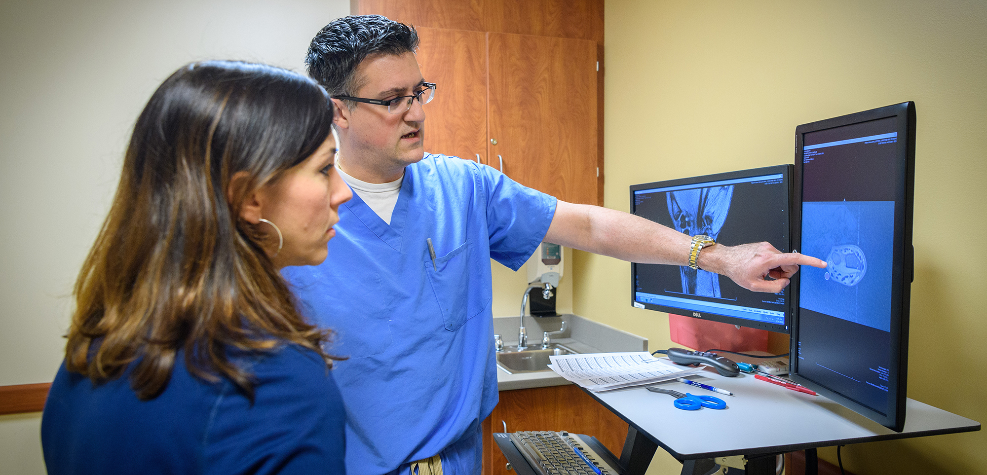 Dr. Joel Ferreira looking at an MRI with a patient