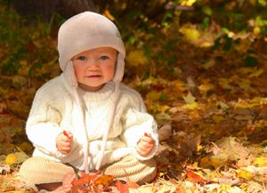 Baby smiling and sitting in fall leaves
