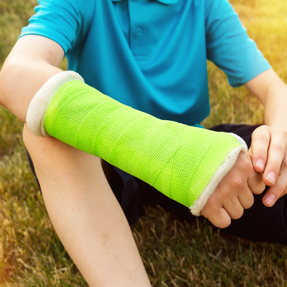 Young boy making with a broken arm in a cast