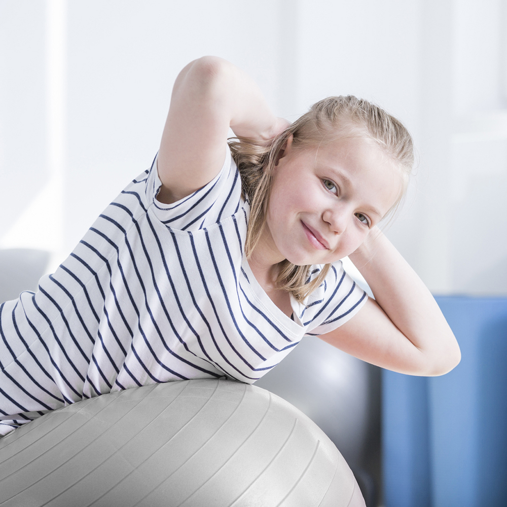 Child smiling at camera laying on ball during physical therapy session