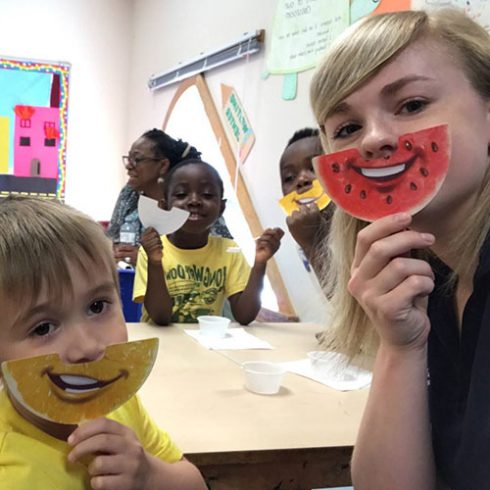 "A UConn undergraduate student and preschool children holding paper ""fruit smiles"" under their noses."