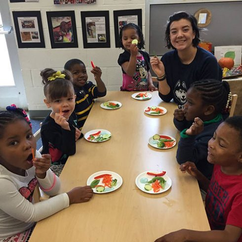 A UConn undergraduate student eating fresh, raw vegetables with preschool children in a classroom in Hartford.