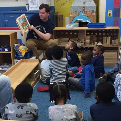 An undergraduate student reading a book to preschool children in a classroom in Hartford.