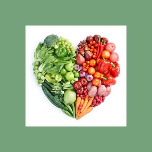 A colorfule photo of fruits and vegetables arranged in the shape of a heart,