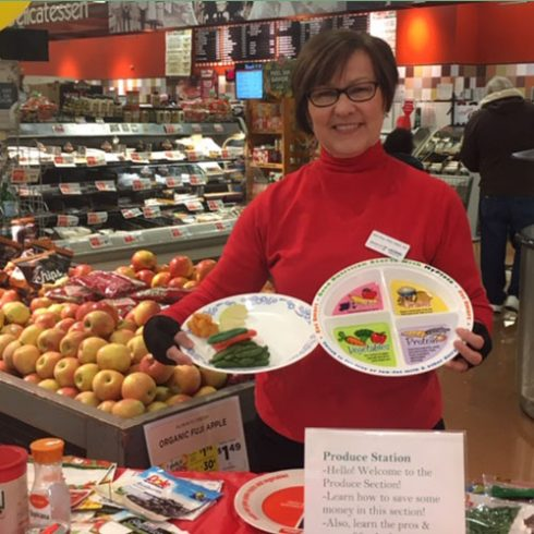 In the grocery store, a dietitian from Husky Programs is holding a plate with portion sizes that is printed with nutrition information (from USDA).