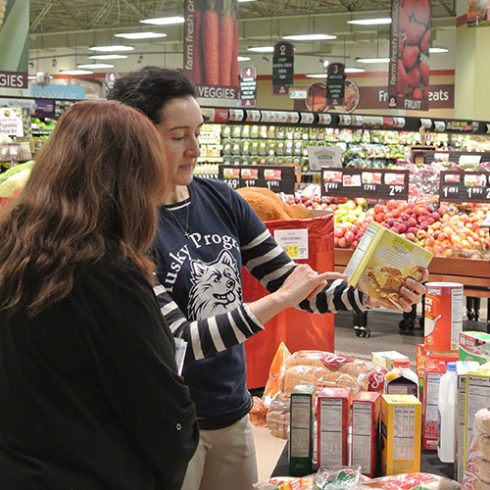 At the grocery store, a dietitian from Husky Programs is reading a Nutrition Facts food label with a customer.
