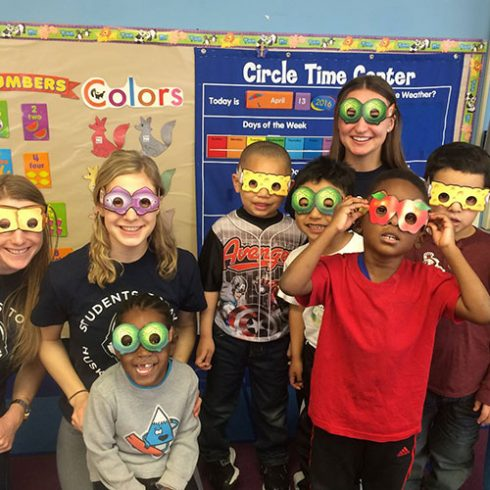 Undergraduate students with children in a classroom sporting goggles/masks with pictures of food printed on the masks.