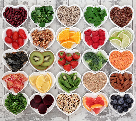 A variety of healthy food choices (fruits, vegetables, nuts, grains) in heart shaped cups arranged 5 by 5 on a weathered wooden floor