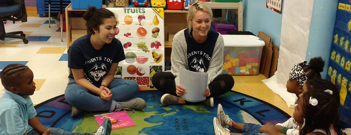 Students reading to little kids in a classroom