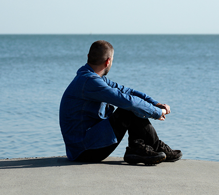Man sitting on a beach staring out to sea