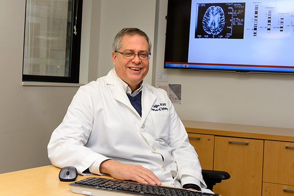 Dr. David Steffens sitting at a table with a keyboard and mouse