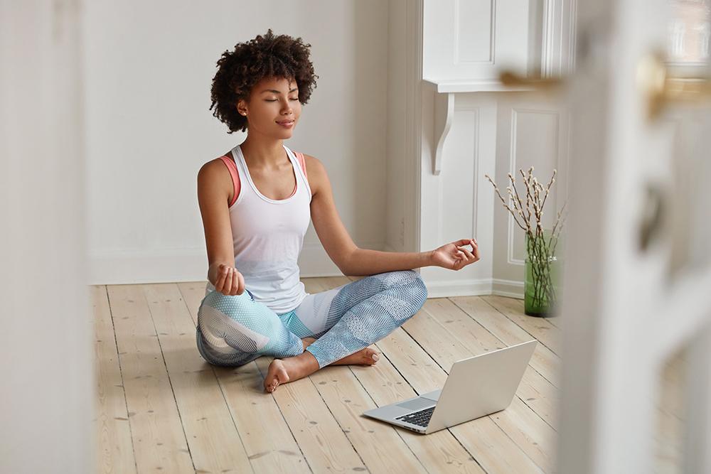 African American woman sitting a floor meditating