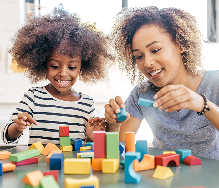 Toddler girl and mother playing with colorful wooden blocks